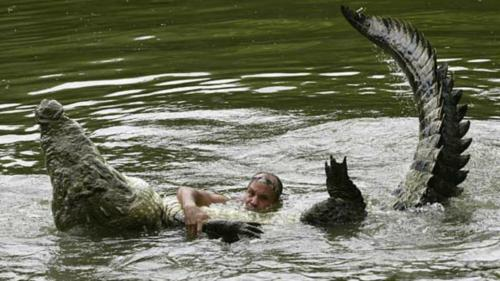 man doing wresling with crocodile in water